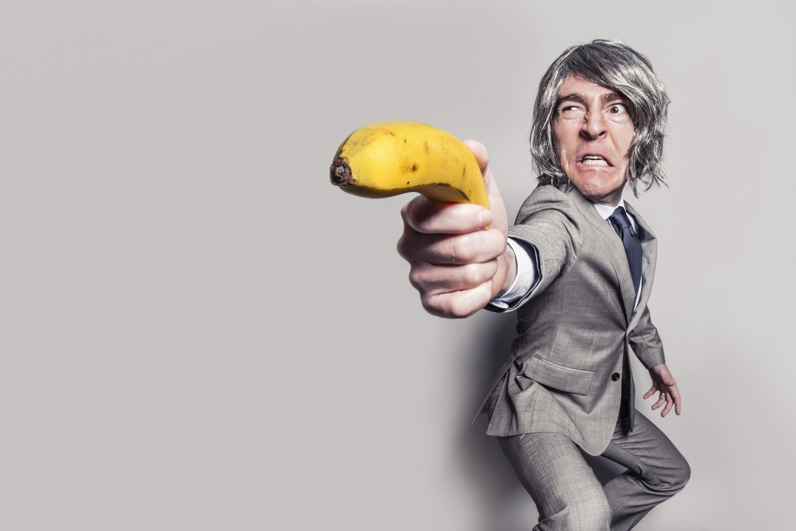 Average look of a business man holding a banana as a weapon